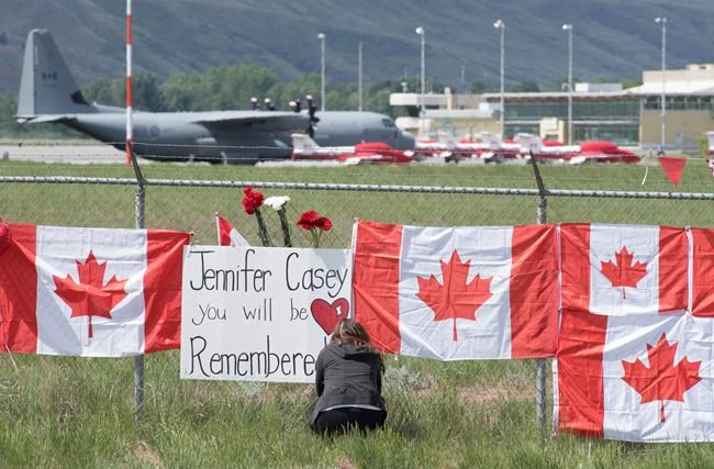 The Canadian Forces Snowbirds jets are seen in the background as a woman attaches a sign to a fence in Kamloops, B.C., Monday, May 18, 2020. The military's Snowbirds are being allowed back into the air after a deadly crash in May saw the aerobatic team's iconic jets grounded in British Columbia for more than three months. THE CANADIAN PRESS/Jonathan Hayward
