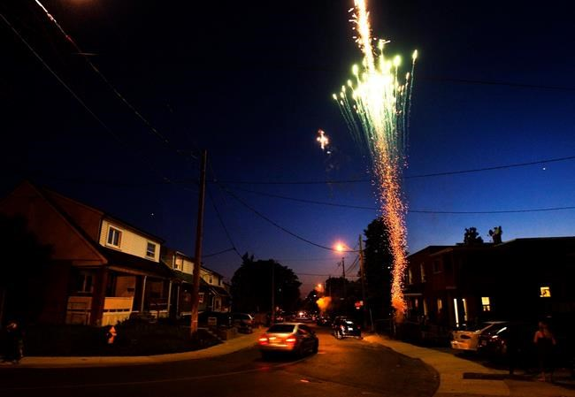 Residents light fireworks along their street during the Victoria Day long weekend in Toronto on Monday, May 24, 2010. The Victoria Day weekend has long been the unofficial kick-off to outdoor season in Canada. But the COVID-19 pandemic has upended nearly every element of Canadian life, as physical distancing requirements forced the partial shutdown of the economy. THE CANADIAN PRESS/Nathan Denette