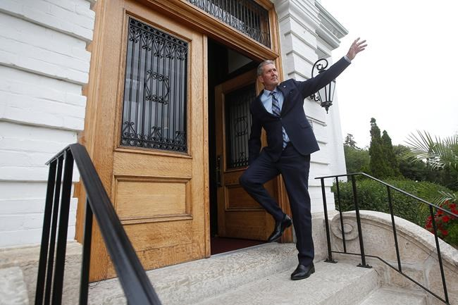 Manitoba Premier Brian Pallister waves as he enters the Lieutenant Governor's home to drop the writ calling for a September election.  (John Woods / THE CANADIAN PRESS)