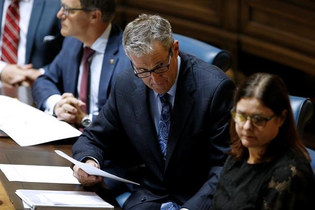 Manitoba Premier Brian Pallister talks to ministers after the reading of the Speech from the Throne at the Manitoba Legislature in Winnipeg, Monday, September 30, 2019. THE CANADIAN PRESS/John Woods