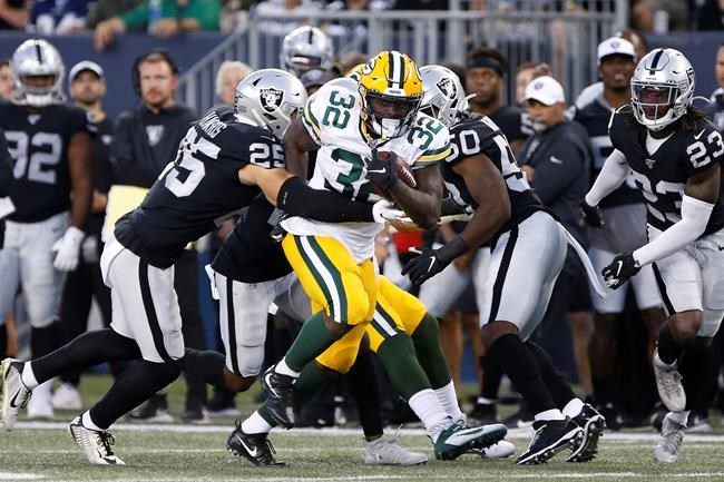 Green Bay Packers' Tra Carson (32) makes yards as Oakland Raiders' Erik Harris (25) attempts the tackle during the first half of NFL pre-season action in Winnipeg Thursday, August 22, 2019. THE CANADIAN PRESS/John Woods