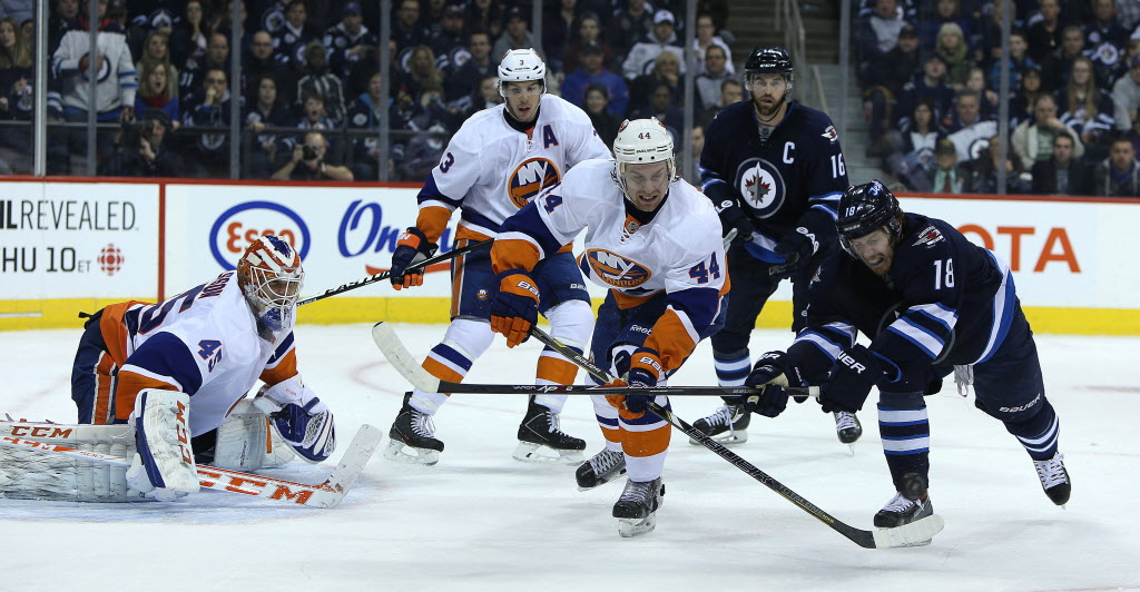 Winnipeg Jets forward Bryan Little tries in vain to beat New York Islanders defenceman Calvin de Haan to the puck during second-period action.