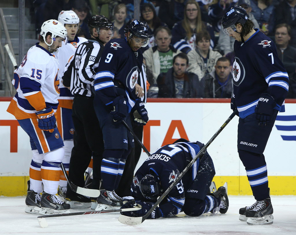 Winnipeg Jets forward Evander Kane and defenceman Keaton Ellerby look at Mark Scheifele after he was injured during the second period. (Jason Halstead / Winnipeg Free Press)