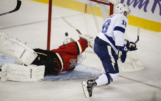 Tampa Bay Lightning Ondrej Palat, right, from the Czech Republic, scores the game winning goal as Calgary Flames goalie Karri Ramo, from Finland, dives for the puck during overtime NHL hockey action in Calgary, Tuesday, Oct. 21, 2014.THE CANADIAN PRESS/Jeff McIntosh