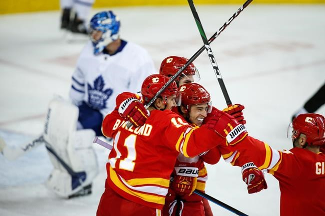 Toronto Maple Leafs goalie Frederik Andersen, left, looks away as Calgary Flames' Johnny Gaudreau, centre right, celebrates his goal with teammates during third period NHL hockey action in Calgary, Thursday, Dec. 12, 2019.THE CANADIAN PRESS/Jeff McIntosh