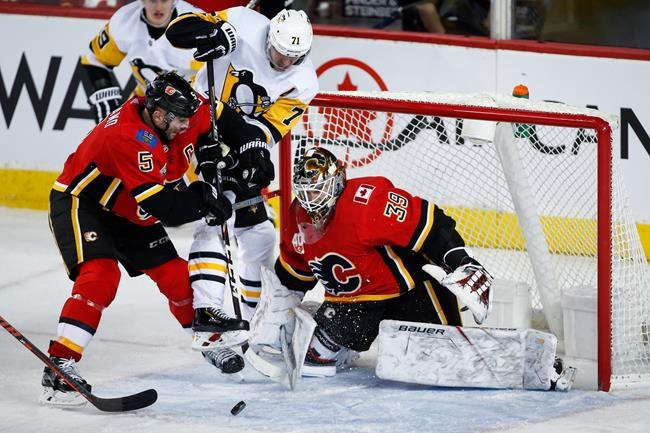Pittsburgh Penguins' Evgeni Malkin, ceentre, tries to get to the puck between Calgary Flames goalie Cam Talbot, right, and Mark Giordano during third period NHL hockey action in Calgary, Tuesday, Dec. 17, 2019.THE CANADIAN PRESS/Jeff McIntosh
