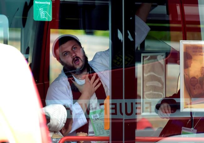 A man, wearing traditional Jewish clothing, reacts after he was escorted by the police to a bus at a Jewish cemetery and synagogue in Halle, Germany, Wednesday, Oct. 9, 2019. A heavily armed assailant tried to force his way into a synagogue Wednesday in eastern Germany on Yom Kippur, Judaism's holiest day, and two people were killed as he fired shots outside the building and into a kebab shop, authorities and witnesses said. (AP Photo Jens Meyer)