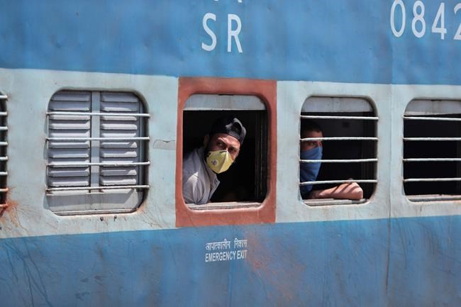 Passengers wearing masks as a precautionary measure against the new virus are seen inside a train in Jammu, India, Monday, March 23, 2020. Authorities have gradually started to shutdown much of the country of 1.3 billion people to contain the outbreak. For most people, the new coronavirus causes only mild or moderate symptoms. For some it can cause more severe illness. (AP Photo/Channi Anand)