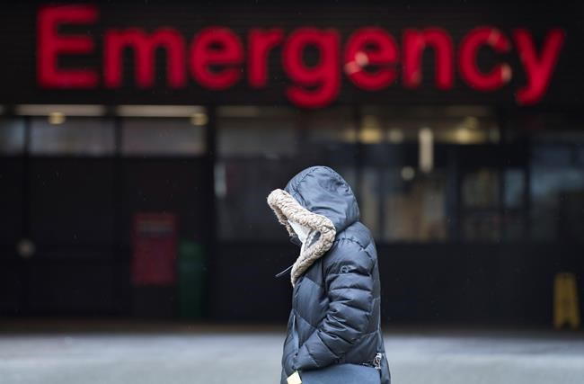 A woman wears a protective face mask as she walks past the Emergency dept. of the Vancouver General Hospital in Vancouver Monday, March 30, 2020. . THE CANADIAN PRESS/Jonathan Hayward