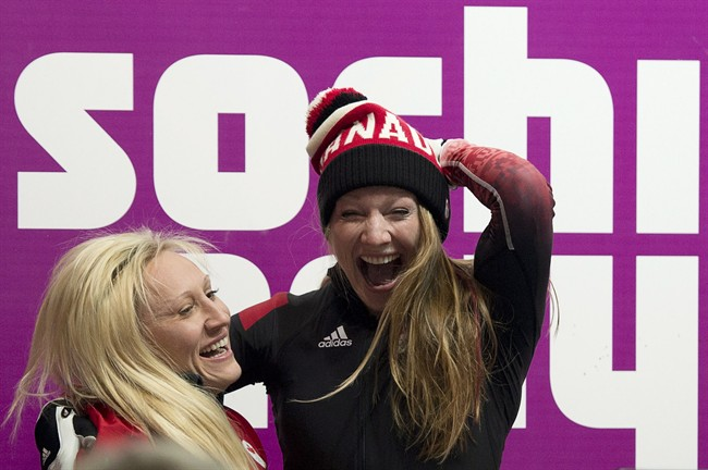 Canada's Kaillie Humphries, left, and Heather Moyse celebrate their gold medal win in women's bobsled at the Sochi Winter Olympics in Krasnaya Polyana, Russia, Wednesday, Feb. 19, 2014. THE CANADIAN PRESS/Jonathan Hayward