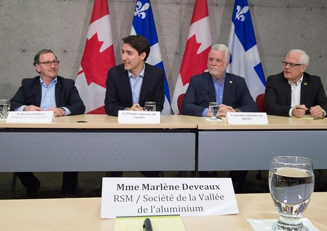 Prime Minister Justin Trudeau, left, speaks at a roundtable meeting with members of the aluminum industry in Saguenay, Que., Monday, March 12, 2018. Saguenay MP Richard Hebert, Quebec Premier Philippe Couillard, centre right, and Dubiuc MNA Serge Simard, right, look on. THE CANADIAN PRESS/Jacques Boissinot