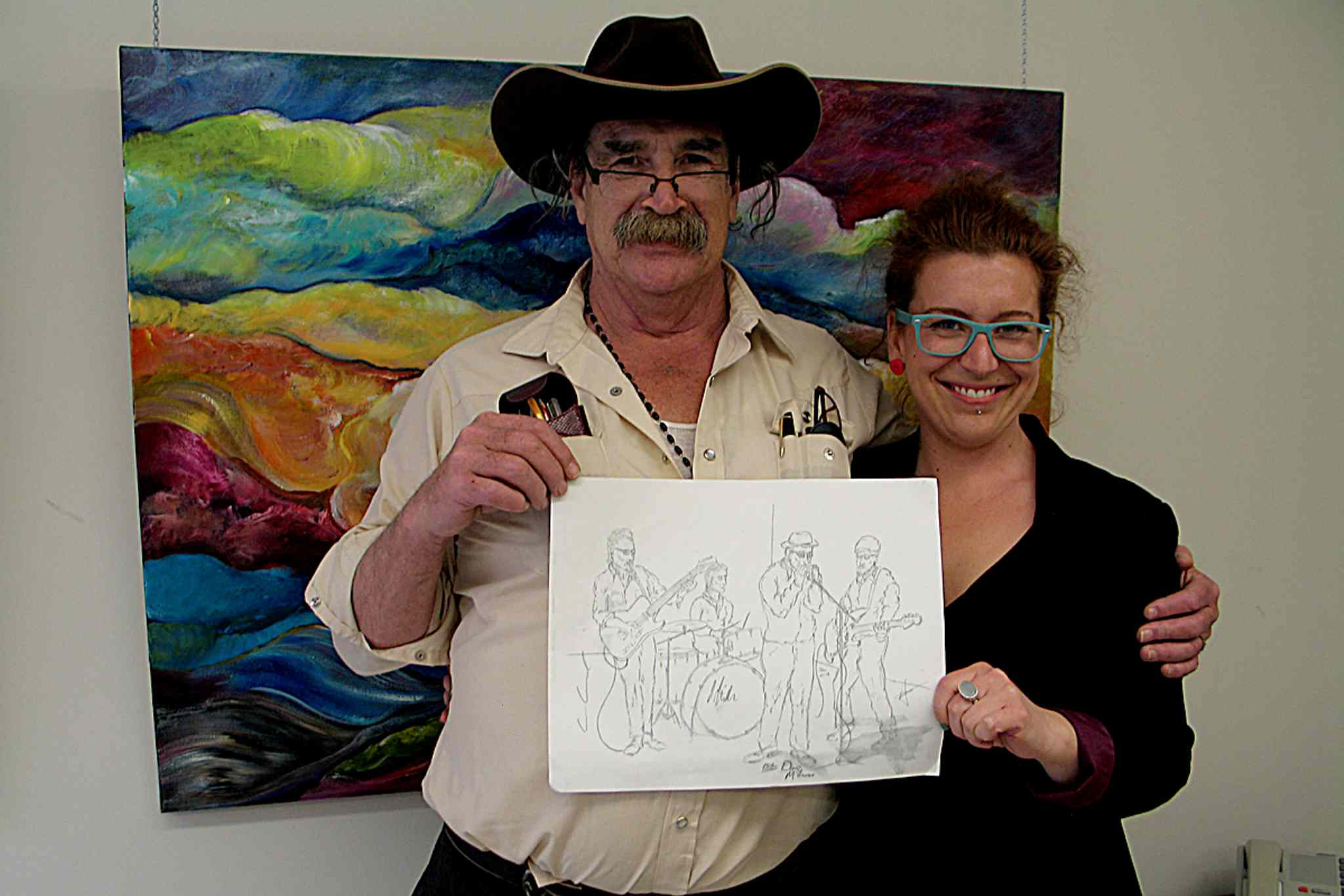 Artist Daniel Lemire (left) and Artbeat employee Rebecca Winkworth display Lemire's sketch of the Sunday night blues jam at Times Change(d). Fourteen Artbeat artists added their own flair to Lemire's sketches for Who's Got Dem Blues? which is on display at Seven Oaks General Hospital.