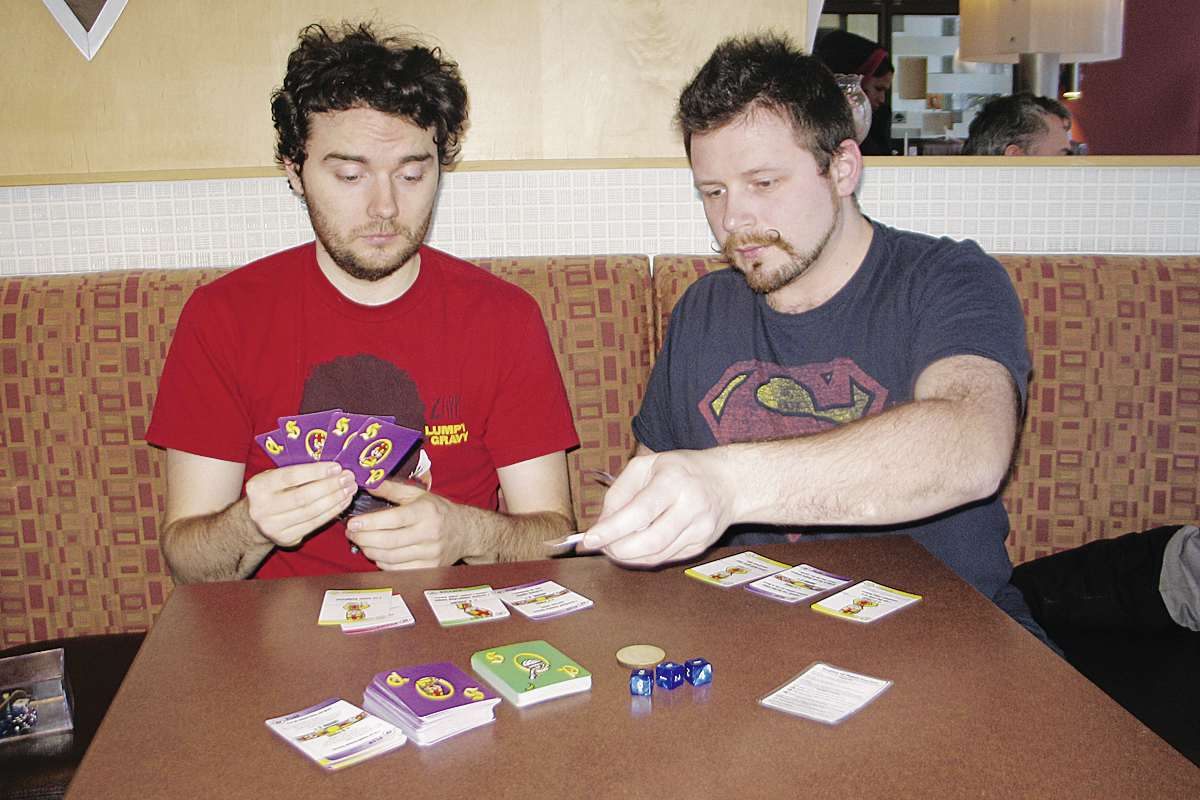 Will O'Donnell (left) and Bart Rucinski play the card game they created, Surplus of Popes.