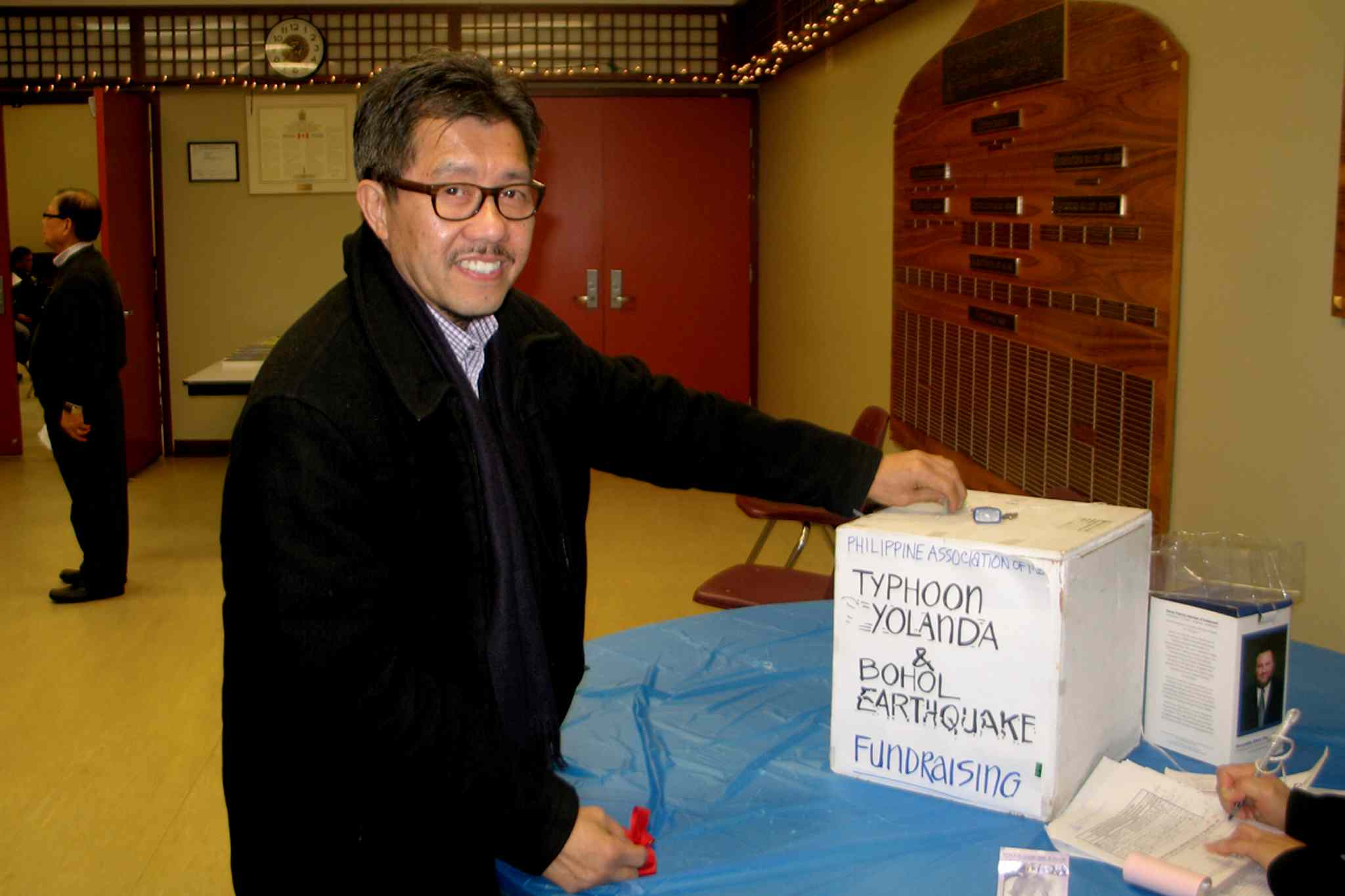 Robert Viray, 59, donating money to Typhoon Haiyan disaster relief. Viray was one of several Winnipeggers at a prayer vigil for typhoon victims at the Philippine Canadian Centre of Manitoba on Nov. 13.