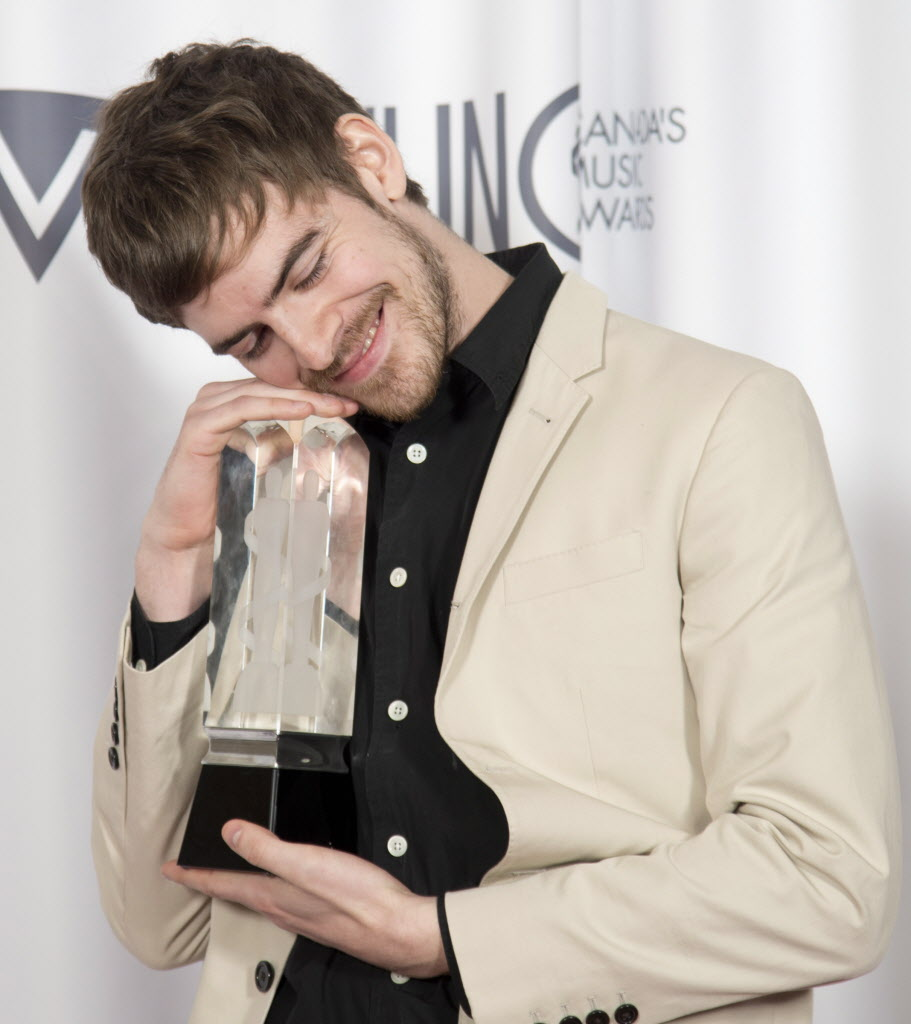 Ryan Hemsworth give his Juno for Electronic Album of the year a loving embrace.  (JONATHAN HAYWARD / THE CANADIAN PRESS )
