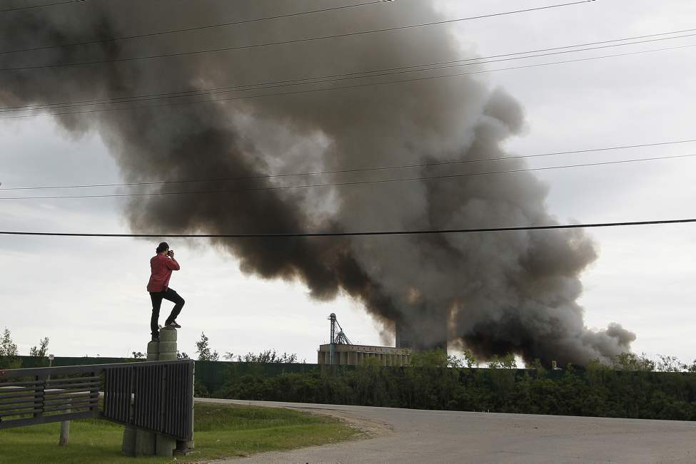 Jed Desilets watches as firefighters from Winnipeg and Springfield rushed to put out a scrap fire at General Scrap on Springfield Road in Winnipeg Tuesday June 12, 2012.  (John Woods / Winnipeg Free Press)