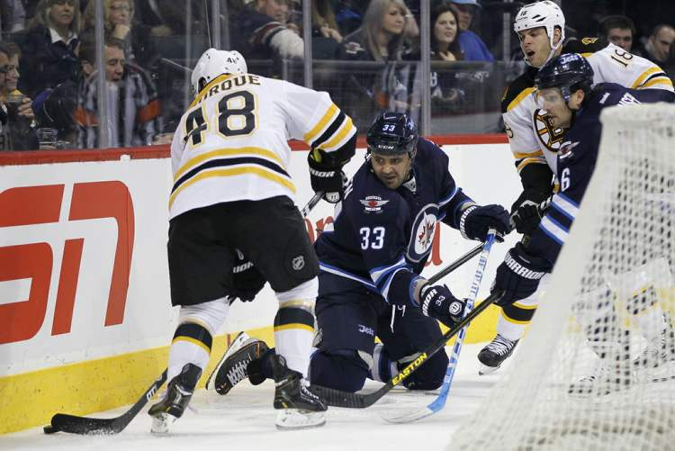 Dustin Byfuglien fights for the puck behind the net with Boston's Chris Bourque with Winnipeg Jets' Ron Hainsey (6) and Bruins' Nathan Horton close behind during the third period.