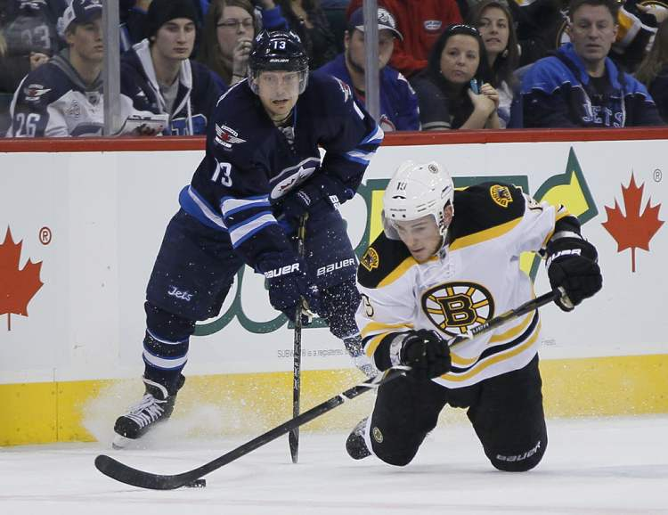 Boston Bruins' Tyler Seguin and Kyle Wellwood fight for the puck during the third period. (JOHN WOODS / WINNIPEG FREE PRESS)