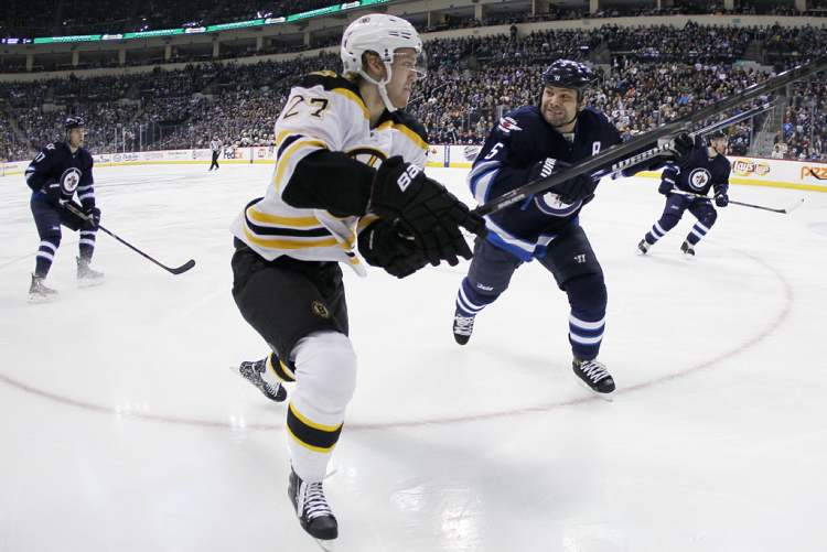 Mark Stuart lines up Boston's Dougie Hamilton during the first period. (JOHN WOODS / WINNIPEG FREE PRESS)
