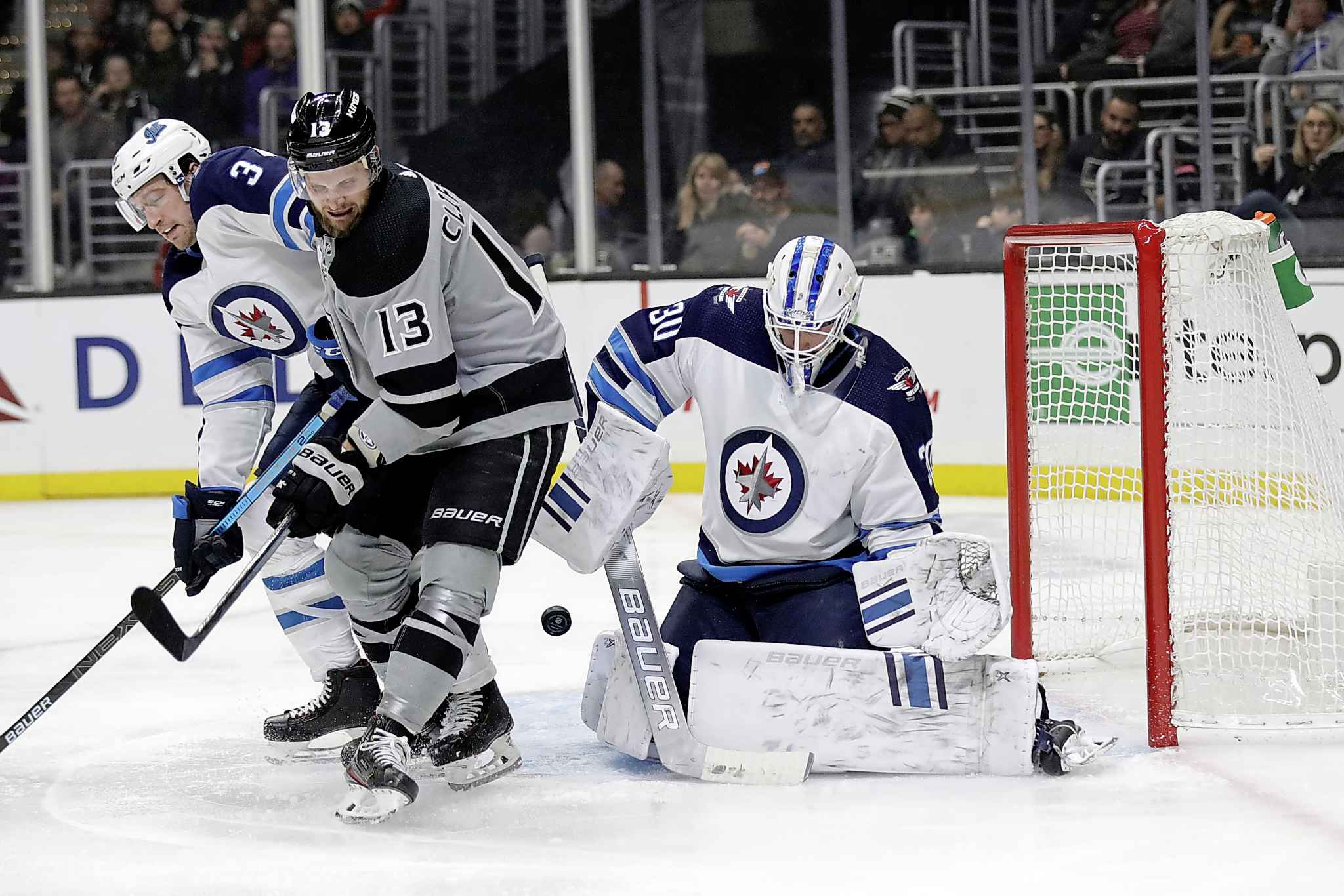 The puck bounces in front of the goal between Winnipeg Jets' Tucker Poolman, left, Los Angeles Kings' Kyle Clifford (13) and Jets goaltender Laurent Brossoit during the second period of the November 30 game in Los Angeles. (Marcio Jose Sanchez / AP Photo)