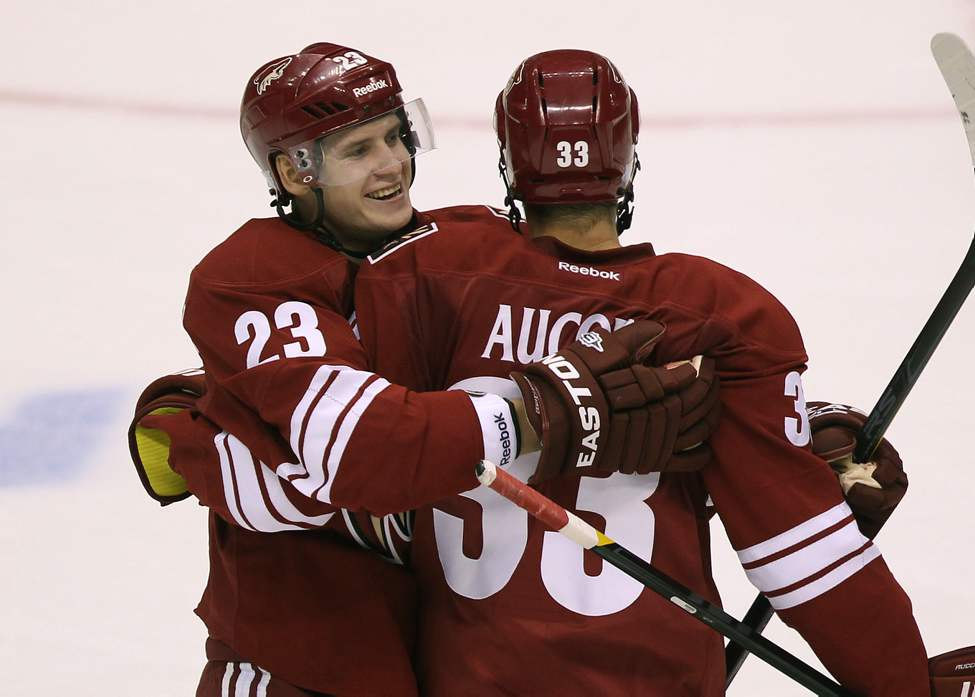 Phoenix Coyotes' Oliver Ekman-Larsson , left, is congratulated by teammate Adrian Aucoin after his second period goal at the Jobing.com Arena in Glendale, Arizona. The Coyotes beat the Winnipeg Jets 4-1.   (JOE BRYKSA / WINNIPEG FREE PRESS)