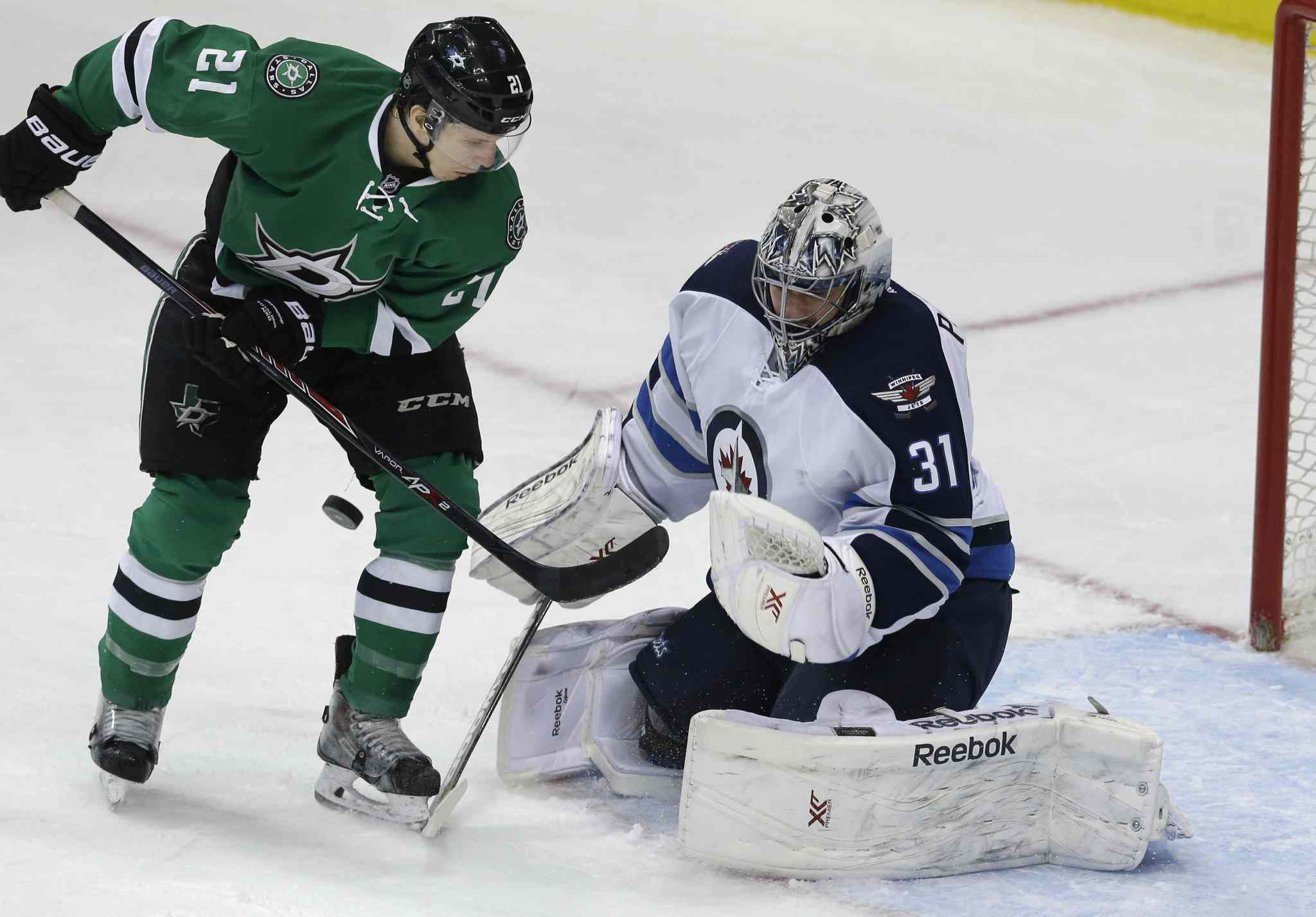 Dallas Stars left wing Antoine Roussel (21) tries to get the puck past Winnipeg Jets goalie Ondrej Pavelec (31) during second period.