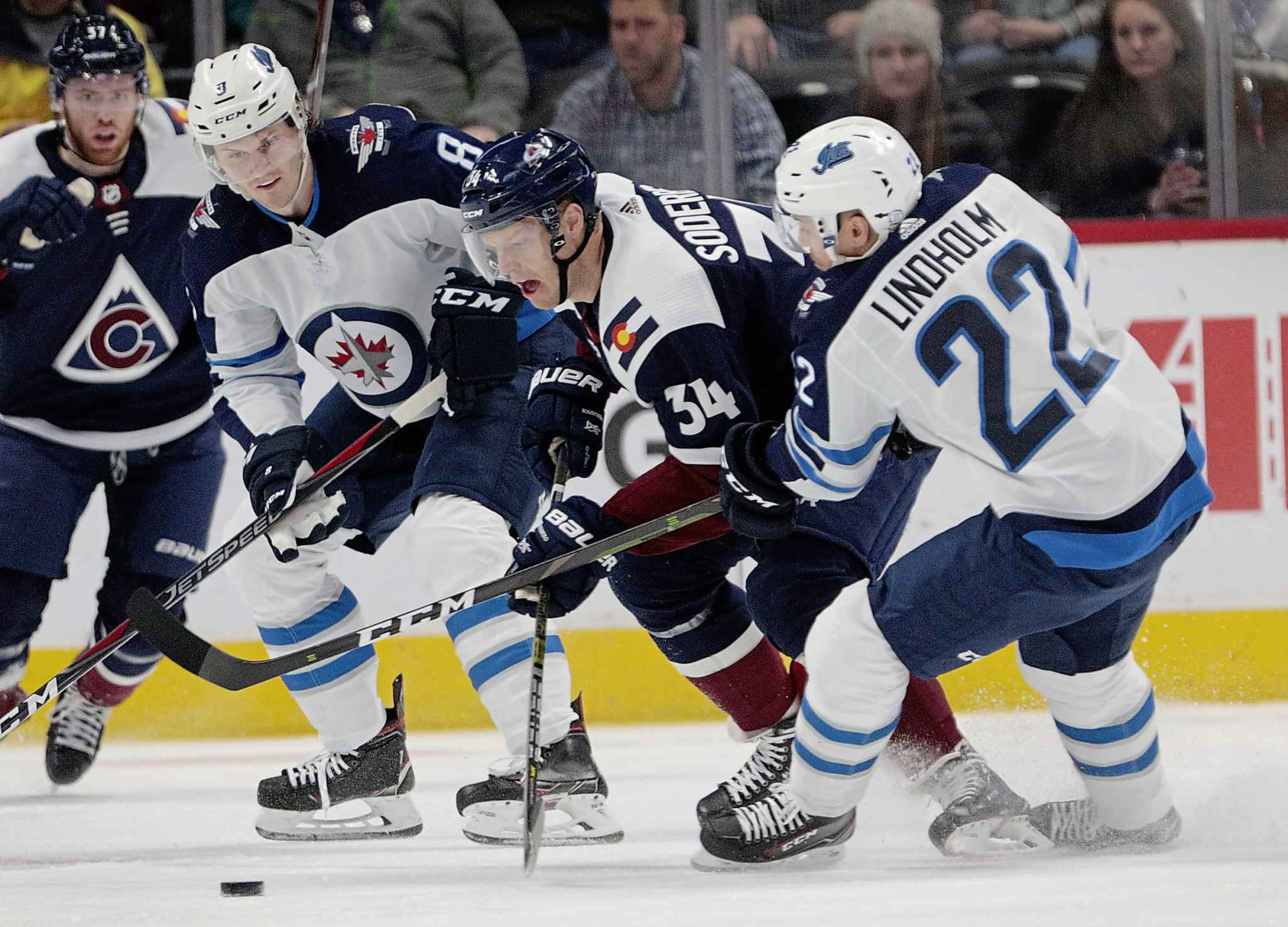 Colorado Avalanche center Carl Soderberg (34) skates between Winnipeg Jets defenseman Jacob Trouba (8) and center Par Lindholm (22) during the first period last night. (AP Photo/Joe Mahoney)