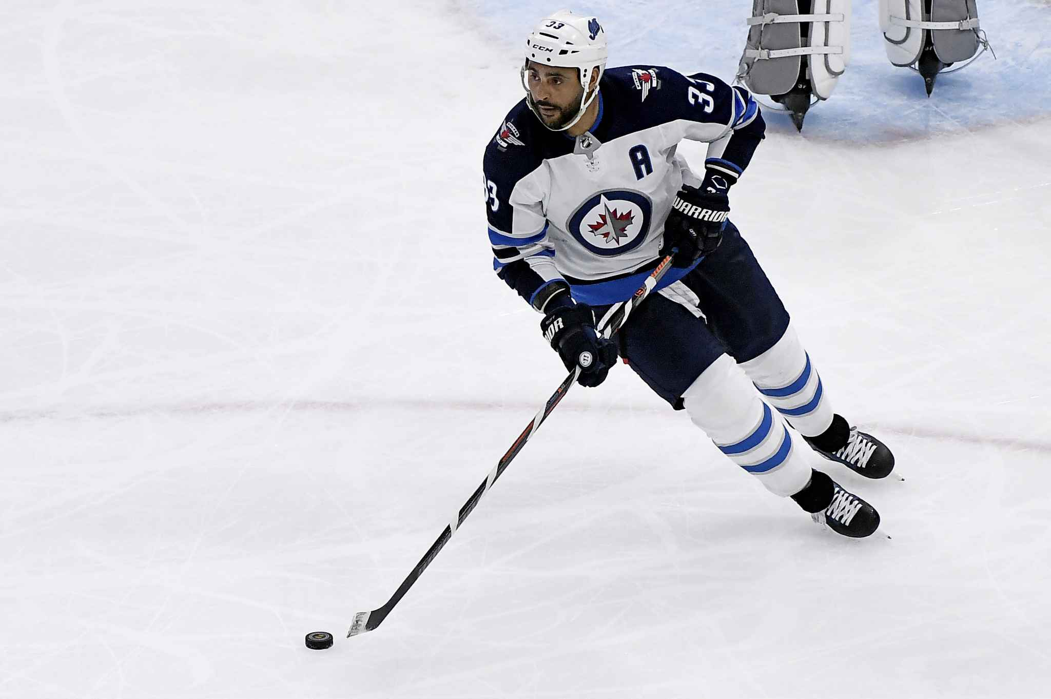Winnipeg Jets defenseman Dustin Byfuglien (33) moves the puck during the second period of an NHL hockey game against the Chicago Blackhawks. (AP Photo/Matt Marton)