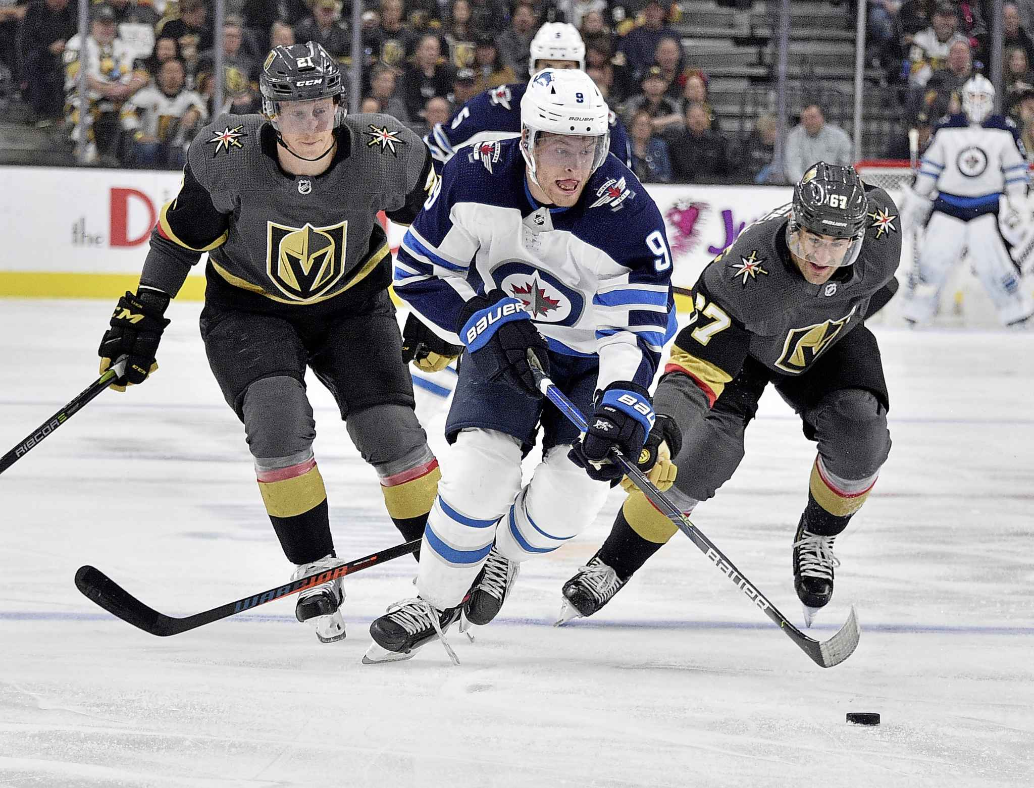 Winnipeg Jets center Andrew Copp (9) skates with the puck against Vegas Golden Knights center Cody Eakin (21) and left wing Max Pacioretty during the first period of an NHL hockey game Saturday, Nov. 2, 2019, in Las Vegas. (AP Photo/David Becker)