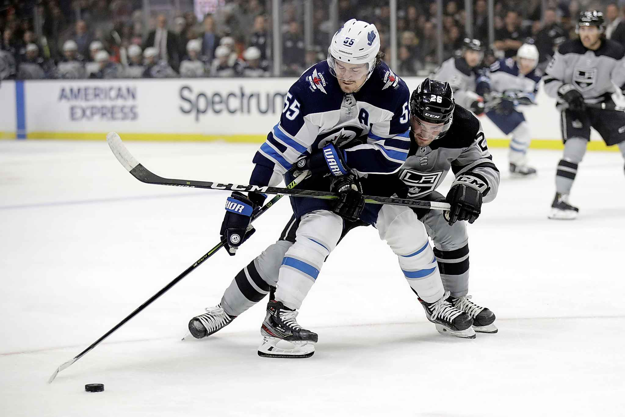 Mark Scheifele works the puck against Sean Walker Saturday in Los Angeles. (Marcio Jose Sanchez / The Associated Press)