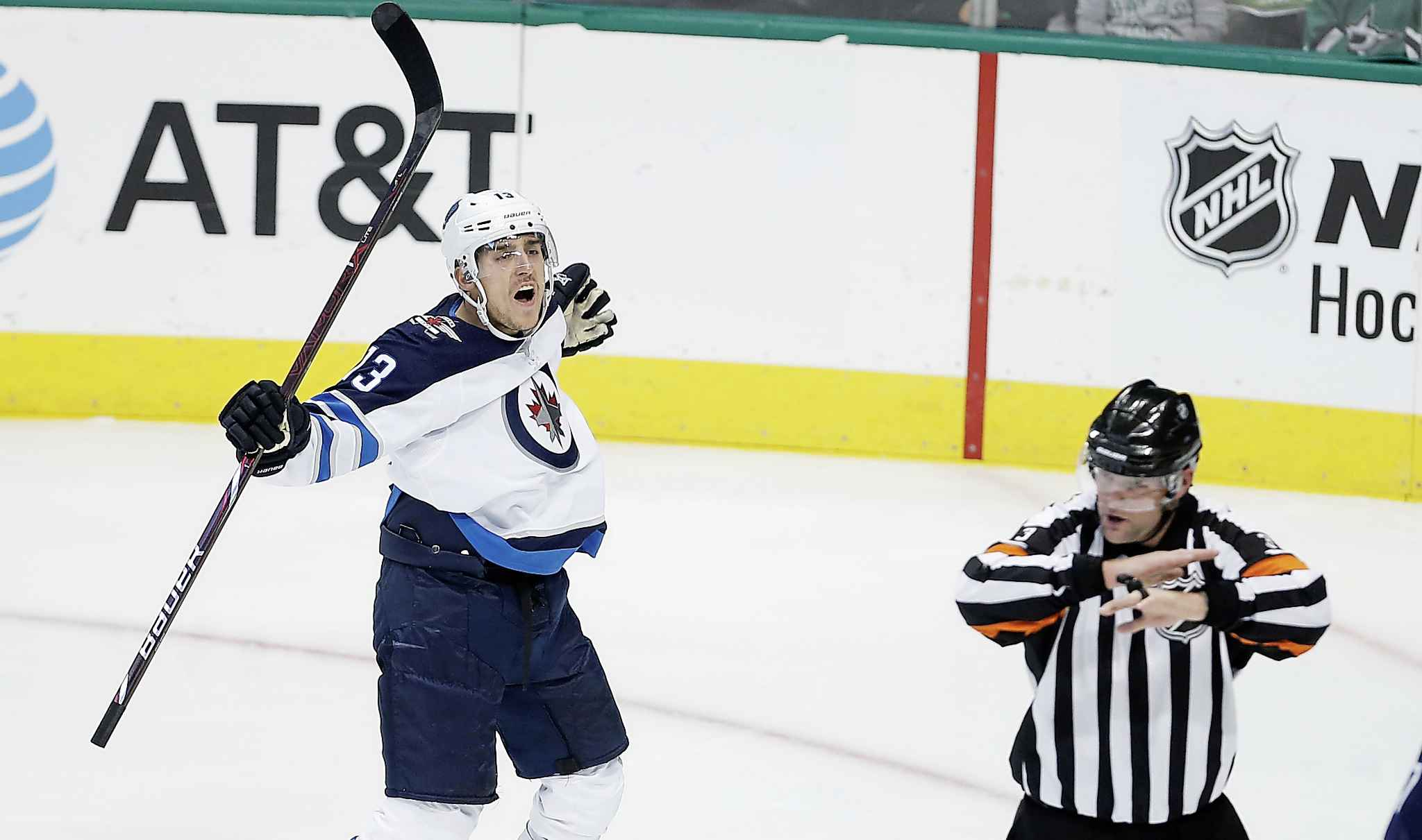 Winnipeg Jets forward Brandon Tanev (13) reacts as referee Chris Schlenker (3) waves off his goal for goaltender interference during the first period of an NHL hockey game against the Dallas Stars, Saturday, Oct. 6, 2018, in Dallas.