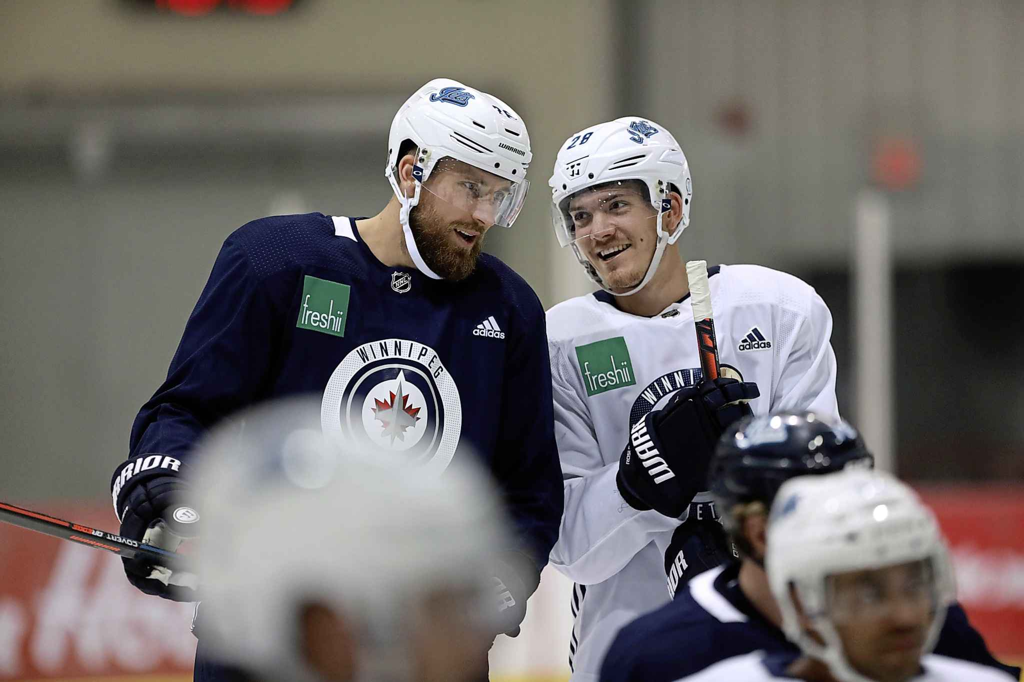 Winnipeg Jets captain Blake Wheeler, left, is all smiles while talking to young centreman Jack Roslovic during a workout at MTS Iceplex Tuesday.
