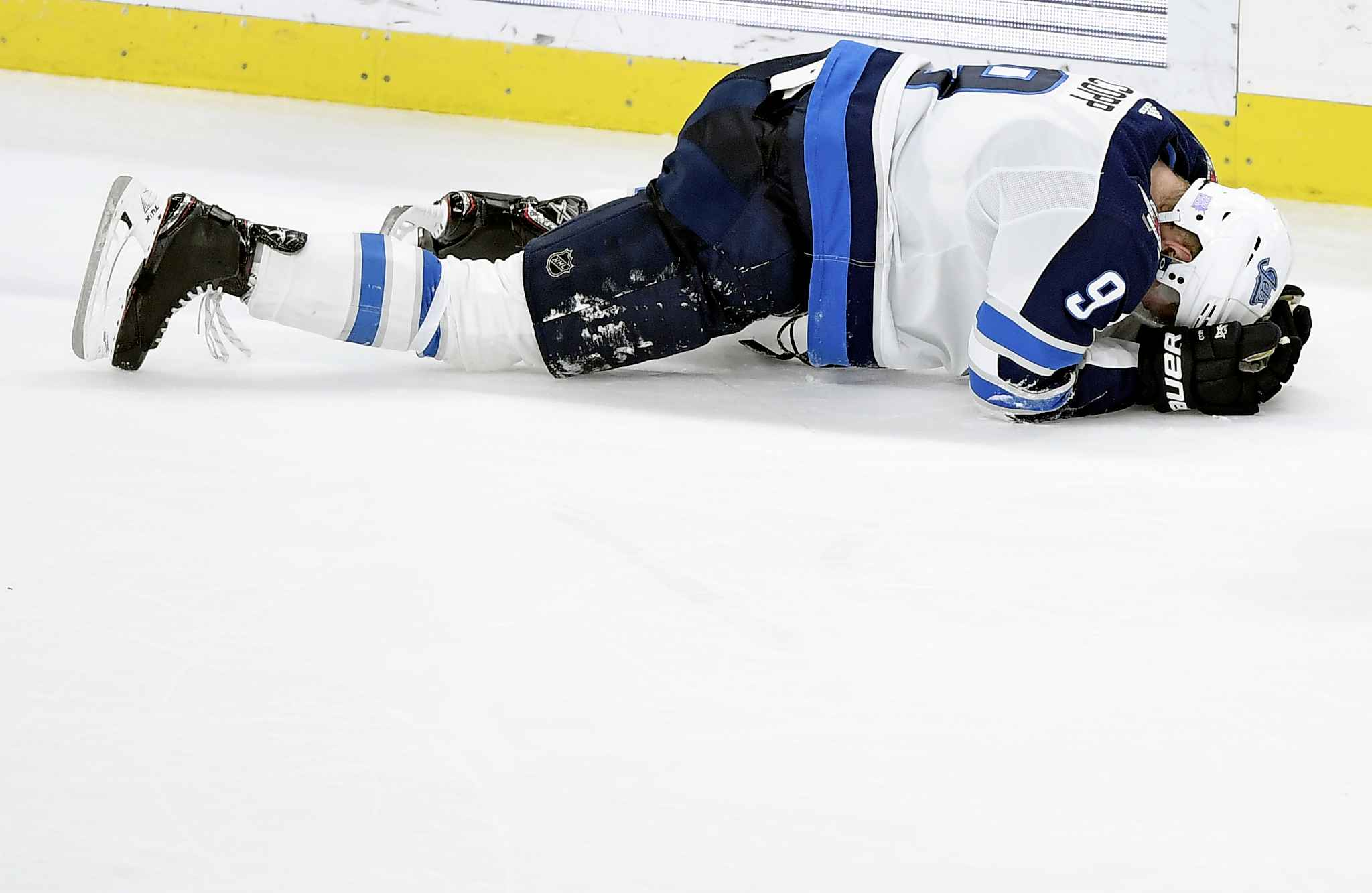 Winnipeg Jets's Andrew Copp (9) lays on the ice after a check by Minnesota Wild's J.T. Brown (23), not pictured, during the third period of an NHL hockey game Friday, Nov. 23, 2018, in St. Paul, Minn. Copp left the game. The Wild won 4-2. (AP Photo/Hannah Foslien)
