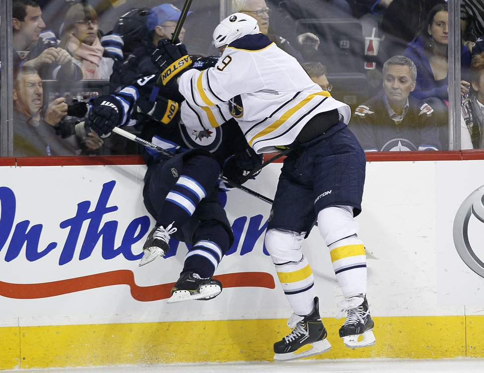 Winnipeg Jets' Tobias Enstrom (39) gets smashed into the boards by Buffalo Sabres' Steve Ott (9) during first period NHL action in Winnipeg.
