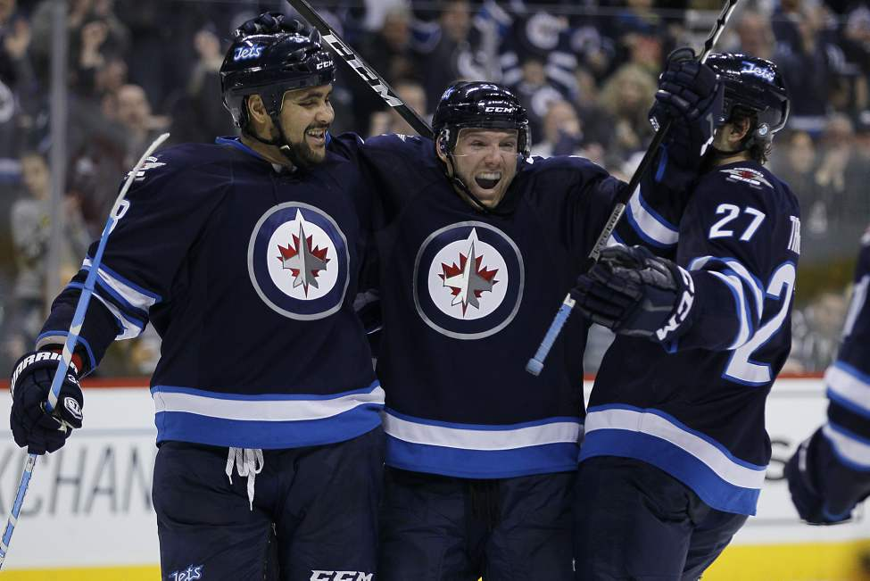 Winnipeg Jets' Aaron Gagnon (21), Dustin Byfuglien (33) and Eric Tangradi (27) celebrate Gagnon's goal against the Buffalo Sabres during second period NHL action in Winnipeg. This was Gagnon's first NHL goal. 