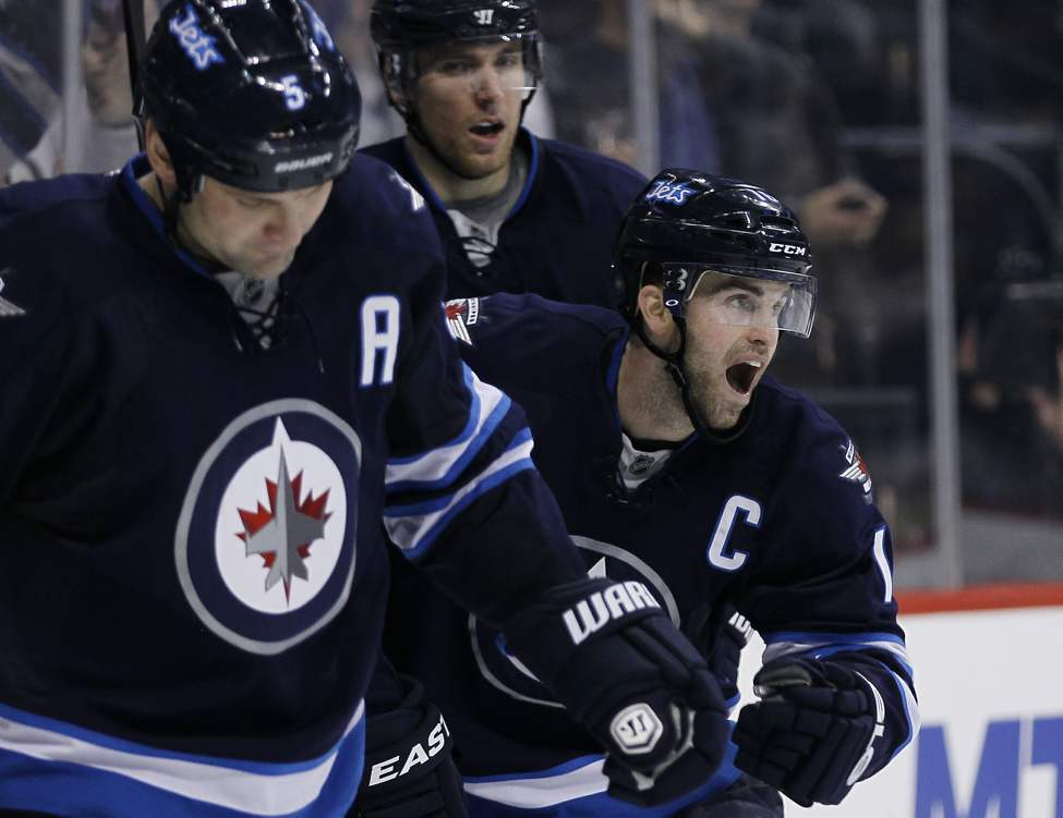 Winnipeg Jets' Andrew Ladd (16), Mark Stuart (5), and Blake Wheeler (26) celebrates Ladd's goal on Buffalo Sabres' goaltender Ryan Miller (30) during second period NHL action in Winnipeg. 
