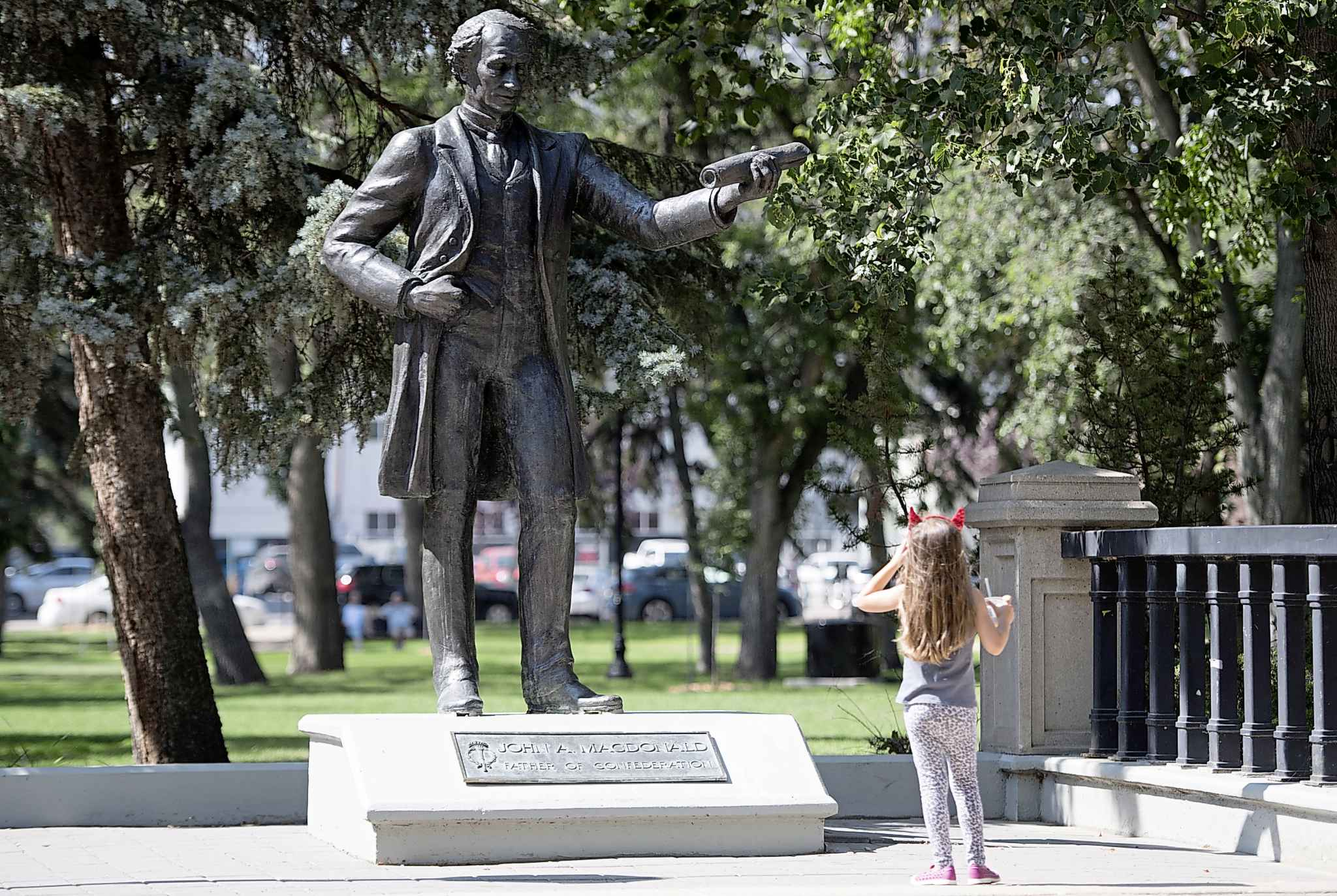 A little girl stops to look at a statue of John A. Macdonald in Victoria Park in Regina. (Jonathan Hayward / The Canadian Press)