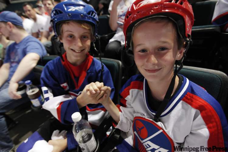 Cayden Kraus (left) and Joey Sabatini celebrate at the NHL draft party at the MTS Centre in Winnipeg Friday after it was announced the new NHL team's name will be the Jets.