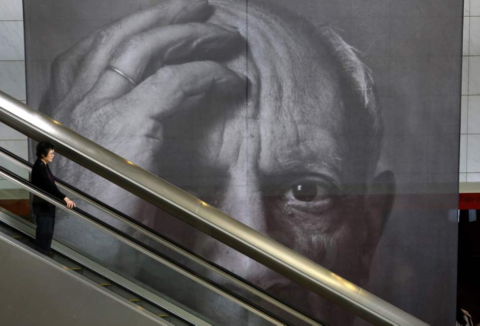 A visitor takes an escalator, passing a giant banner of Pablo Picasso during his exhibition in Hong Kong's Heritage Museum. (AP Photo/Vincent Yu)
