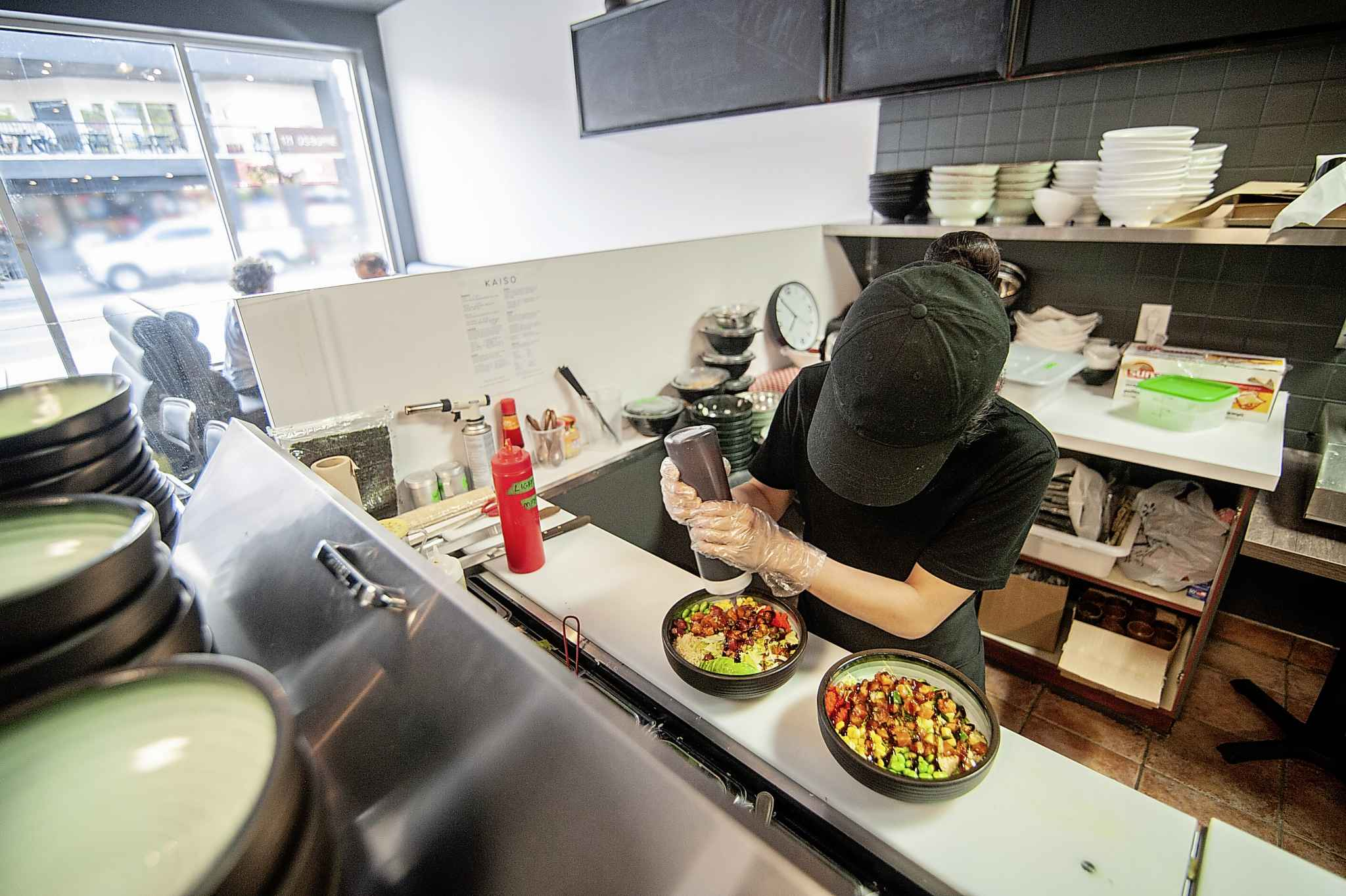 An employee creates a Poke Bowl, a popular choice at the Osbourne Street restaurant. (Mike Sudoma / Winnipeg Free Press)