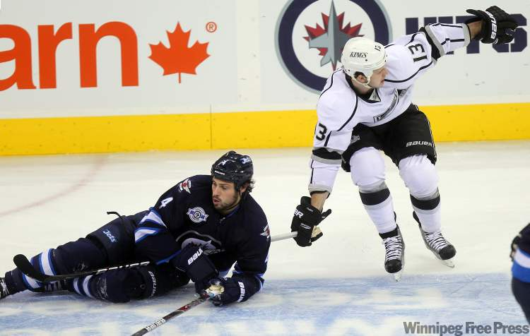 Winnipeg Jets Zach Bogosian keeps King Kyle Clifford's stick firmly under his arm as he trails the L.A. Winger. Bogosian drew a two-minute interference for his effort.