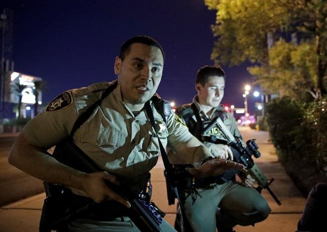FILE - In this Oct. 1, 2017, file photo, police officers advise people to take cover near the scene of a shooting near the Mandalay Bay resort and casino on the Las Vegas Strip in Las Vegas. Tens of thousands of revelers will ring in the New Year in Las Vegas under the close eye of law enforcement just three months after the deadliest mass shooting in modern U.S. history. The Las Vegas Metropolitan Police Department will have every officer working Sunday, Dec. 31, 2017, while the Nevada National Guard is activating about 350 soldiers and airmen. (AP Photo/John Locher, File)