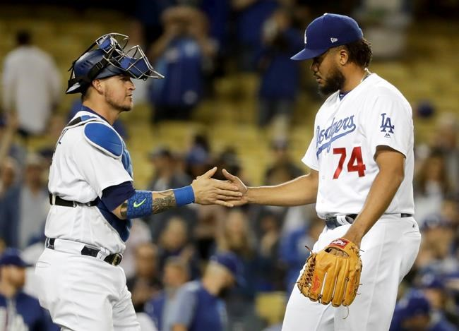 Los Angeles Dodgers relief pitcher Kenley Jansen and catcher Yasmani Grandal celebrate after their 7-2 win against the Miami Marlins during a baseball game in Los Angeles Thursday