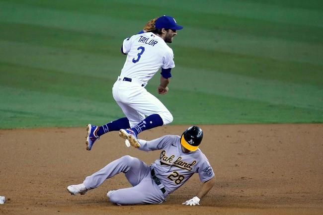 Los Angeles Dodgers second baseman Chris Taylor hops over Oakland Athletics' Matt Olson, who was forced out on a double play hit into by Ramon Laurean during the second inning of a baseball game Thursday, Sept. 24, 2020, in Los Angeles. (AP Photo/ Marcio Jose Sanchez)
