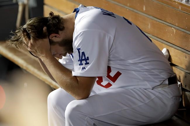 Los Angeles Dodgers pitcher Clayton Kershaw sits in the dugout after giving up back-to-back home runs to the Washington Nationals during the eighth inning in Game 5 of a baseball National League Division Series on Wednesday, Oct. 9, 2019, in Los Angeles. (AP Photo/Marcio Jose Sanchez)
