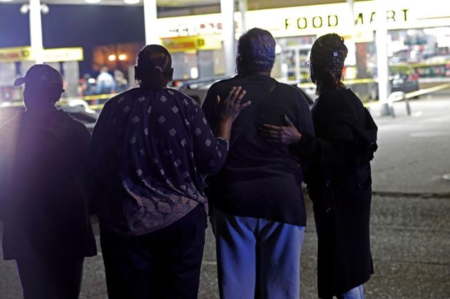 A woman is comforted by others as police investigate the scene of a Mardi Gras day shooting that left at least one dead and others injured, in the lower ninth ward in New Orleans, Tuesday, Feb. 13, 2018. (AP Photo/Gerald Herbert)