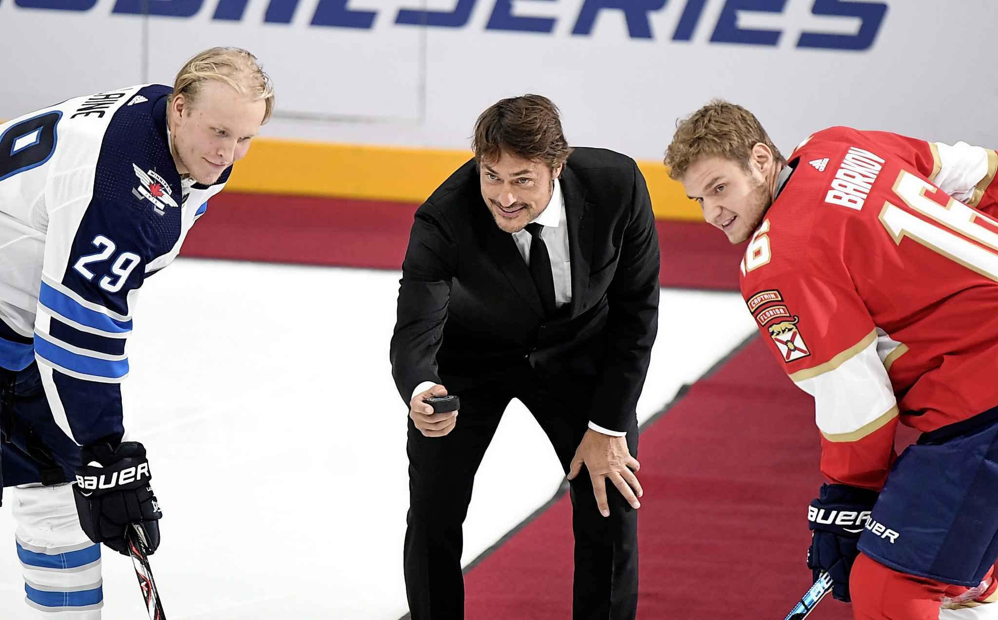 Retired NHL star Teemu Selanne drops the puck during a ceremonial faceoff between Patrik Laine, left, of the Winnipeg Jets and Aleksander Barkov of the Florida Panthers prior to the NHL Global Series in Helsinki, Finland on Thursday.