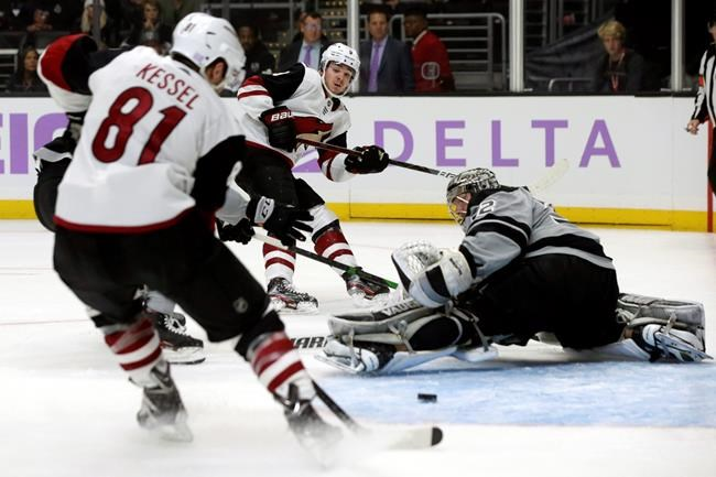 Arizona Coyotes center Clayton Keller's, top center, pass gets by Los Angeles Kings goaltender Jonathan Quick, right,as center Phil Kessel, left, readies ti hit the puck for a goal during the first period of an NHL hockey game in Los Angeles, Saturday, Nov. 23, 2019. (AP Photo/Alex Gallardo)