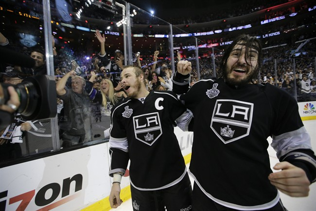 Los Angeles Kings right wing Dustin Brown, left, and teammate defenseman Drew Doughty celebrate after beating the New York Rangers in overtime in Game 5 of the NHL Stanley Cup Final series Friday, June 13, 2014, in Los Angeles. (AP Photo/Jae C. Hong)