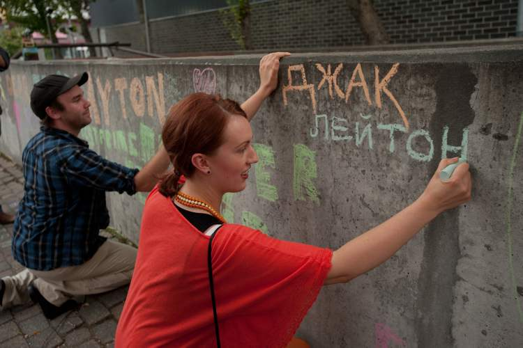 Svitlana Maluzynsky writes Jack Layton's name in Ukranian at a downtown Winnipeg memorial Wednesday, one year after the NDP leader's death.
